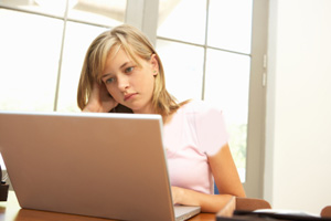 Worried Looking Teenage Girl Using Laptop At Home